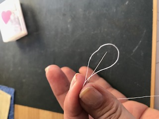 How to make a widows knot - Thread the needle back into the loop